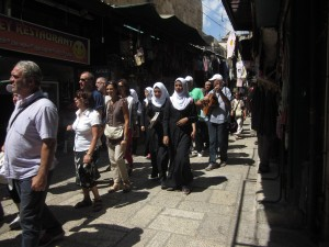 Muslim women and Christian pilgrims walk in the quarter.